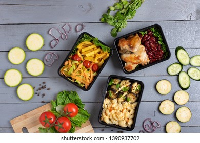 ready grilled dishes into lunch boxes, vegetables set on grey rustic table, top view