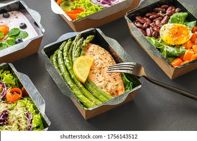 Ready healthy food catering menu in lunch boxes fish and vegetable packages as daily meal diet plan courier delivery with fork isolated on black table background. Take away containers order concept.