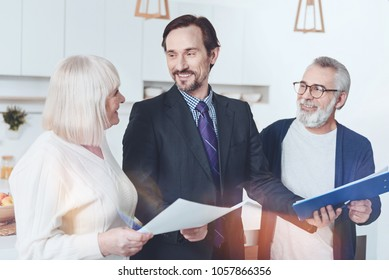 Ready to help. Positive professional delighted insurance agent smiling and meeting with pleasant elderly couple while holding papers