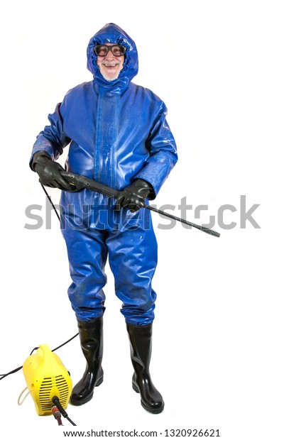 Ready for the high pressure cleaning. A workman in protective suit, rubber gloves, rubber boots and goggles  is ready for the clean with his pressure washer.