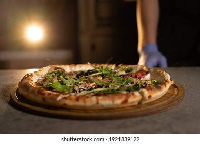Ready hot Italian pizza lies on a wooden board on the table in the kitchen. Lighted oven in the background. Ready meal for dinner. Place for text.