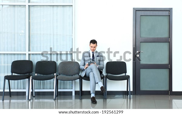 Ready for interview. Thoughtful  man in formalwear holding paper while sitting at the chair in waiting room