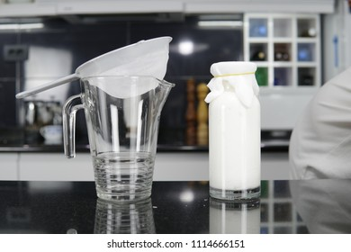 ready kefir drink in a glass bottle with cloth cower and glass bowl with strainer for separating grains from liquids on kitchen top with kitchen in background