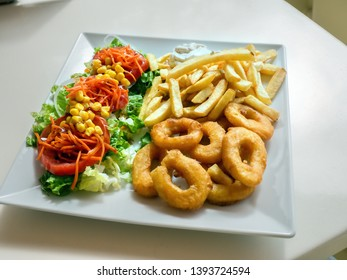 ready meal on a white plate, french fries, salad and squid rings deep fried