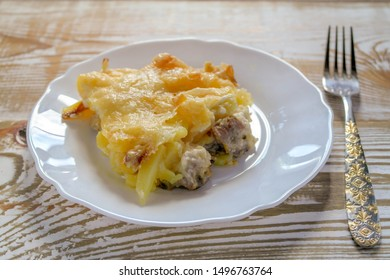Ready meal - the Orlov-style meat with a piece cut off on a white plate. Freshly prepared dish with cut and close-up layers.