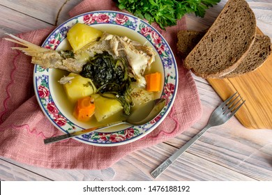Ready meals. Fish soup in a plate from grouper (Epinephelus aeneus) on a wooden table close-up