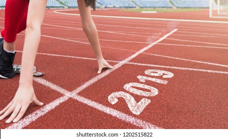 Ready for New Year. Athlete starting line on running track with 2019 year.