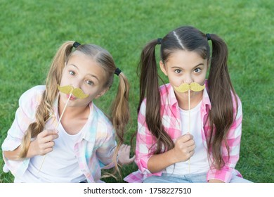 Ready for party. Little children hold mustache props green grass. Small girls with photobooth props on sticks. Party props and accessories. Perfect props for celebration. Summer holidays.