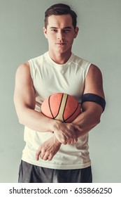 Ready to play. Handsome young man holding basketball ball and looking at camera on gray background.