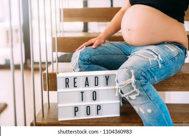 Ready to pop concept - pregnant woman portrait with close up of belly on stairs in home