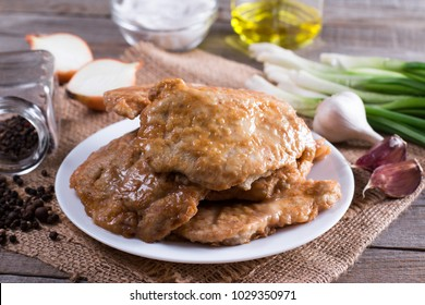 Ready pork chop in a plate on a wooden table