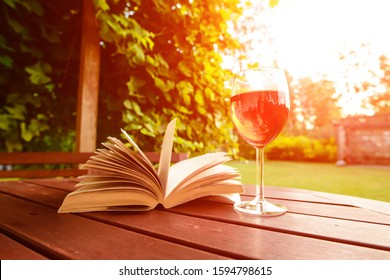 Ready to relax with a glass of rose wine and a book on a wooden table in the garden at sunset. Garden reading table place for relaxation