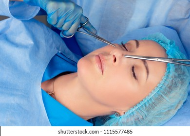Ready for rhinoplasty. People, cosmetology, plastic surgery and beauty concept - surgeon or beautician hands touching woman nose with medical tools instruments preparing for nose job in medical clinic
