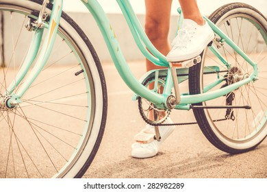 Ready to ride. Close-up of young woman holding her foot on bicycle pedal