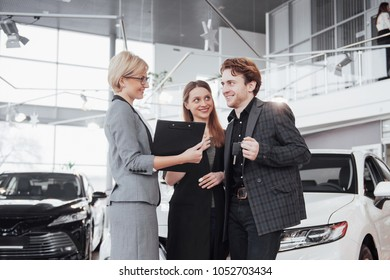 Ready to ride! Gorgeous loving couple posing together near their new car at the car dealership showroom salon smiling happily showing their car keys transport vehicle rental buying wellbeing lifestyle