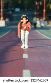 Ready to run. Little girl standing on start line while running outdoor. little girl listen music. Mp3 player. happy little girl. Audio book. Kid in headphones. out for a run. Enjoying a morning run.