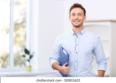 Ready to sale. Pleasant cheerful handsome realtor holding folder and expressing positivity while standing near window