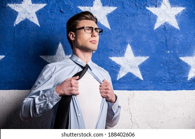 Ready to save the world. Confident young man in formalwear undressing his shirt and looking away while standing against background