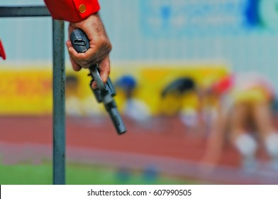 Ready. Set. Go! The starter's pistol is poised at the start of a 200m sprint race.