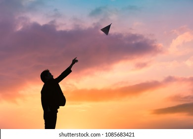 Ready set take off. Man launching paper airplane into the sky.