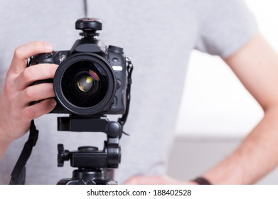 Ready to shoot. Close-up of man holding digital camera while standing in studio with lighting equipment on background