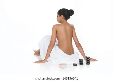 Ready for SPA treatment. Rear view of beautiful young women wrapped in towel looking away while sitting near the SPA stones