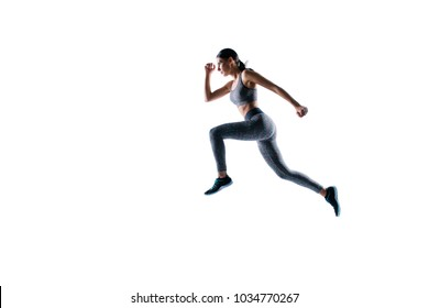 Ready steady go! Concept of endurance strength persistence in sport. Full length full size portrait of beautiful sporty energetic active purposeful sportswoman running and jumping, natural light