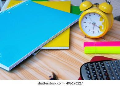 ready to study at the desk with colorful notebooks, calculator, highlighters and a yellow watch