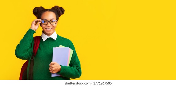 Ready To Study. Portrait of smiling black girl holding glasses, wearing backpack, looking at camera. Panorama, copyspace