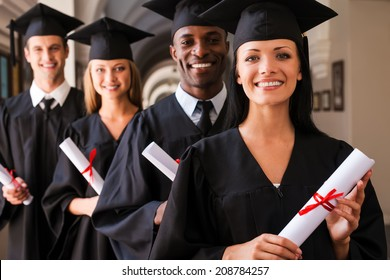 Ready to success. Four college graduates standing in a row and smiling