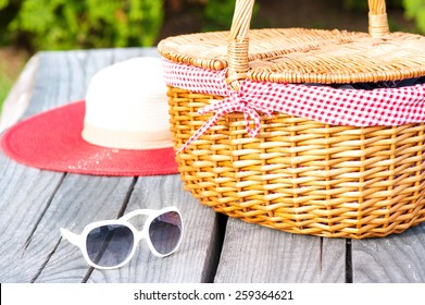 Ready for summer weekend. White sunglasses summer hat and wicker basket on wooden table outdoors.
