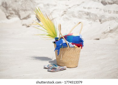 ready for sunbathing and holidays. A bag with a blanket and flip flops on the beach