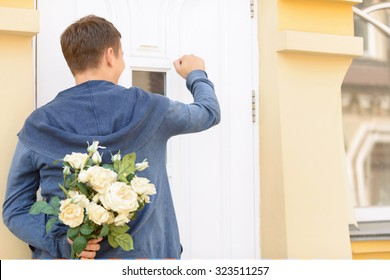 Ready for surprise. Nice cheerful upbeat young guy holding bouquet of flowers and standing near the door while knocking