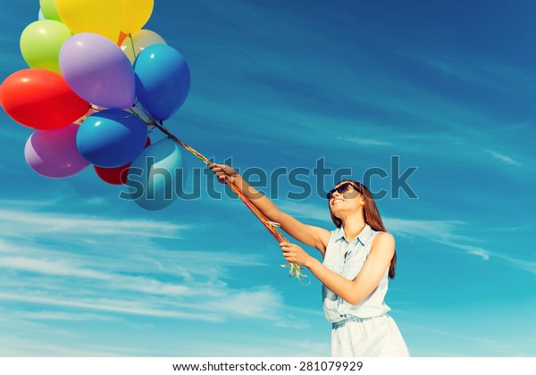 Ready to take off. Low angle view of cheerful young woman holding colorful balloons and smiling while standing against the blue sky