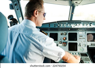 Ready to take off. Rear view of confident male pilot sitting in cockpit and getting an airplane ready to flight