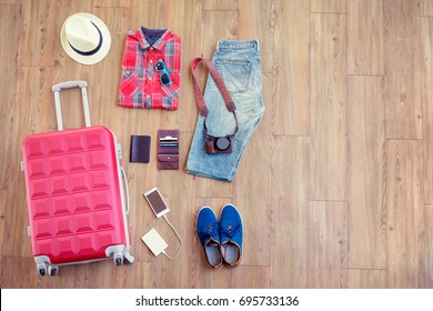 Ready for travel. Essentials for tourist. Different male clothes, accessories and gadgets on wooden floor. Valise, wallet, passport, smartphone and powerbank, shoes, camera, hat.