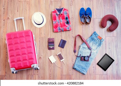 Ready for travel. Essentials for tourist. Top view of male clothes, accessories and gadgets on wooden floor. Valise, wallet, passport, smartphone and powerbank, shoes, camera, hat.