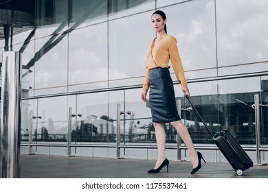 Ready to travel. Full length portrait of pretty brunette lady with suitcase at airport. Copy space in left side