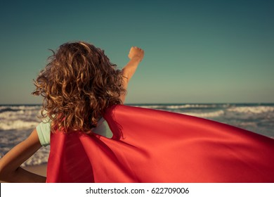 Ready to travel! Superhero child on the beach. Super hero kid having fun outdoor against sea and sky background. Summer vacation concept