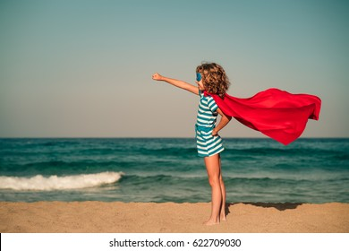 Ready to travel! Superhero child on the beach. Super hero kid having fun outdoor against sea and sky background. Girl power. Summer vacation concept
