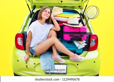 Ready to travel. Young Woman in Green Overloaded Car Luggage Carrier Stuff Things before Trip Bright Suitcases Luggage Full Accessories Clothes Ballon Summer Concept Holiday Adventure Isolated Yellow
