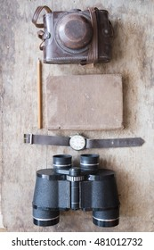 ready for the trip idea, binoculars, notebook, watch and camera on old vintage table
