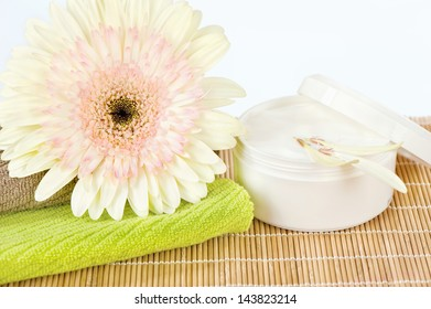 Ready to use skin care product, fresh flower on top of two towels and skin care product