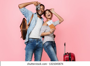 Ready for vacation. Happy couple with suitcase and tickets over pink background