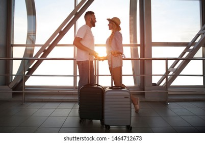 Ready for vacations. Happy couple in airport terminal, waiting for departure, side view
