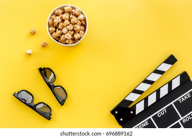 Ready to watch film. Clapperboard, glasses and popcorn on yellow background top view copyspace