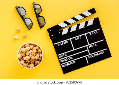 Ready to watch film. Clapperboard, glasses and popcorn on yellow background top view
