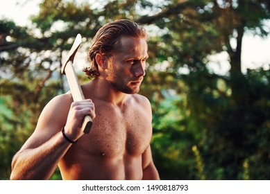 Ready for the work. Confident woodsman. Handsome shirtless man with muscular body type is in the forest at daytime.