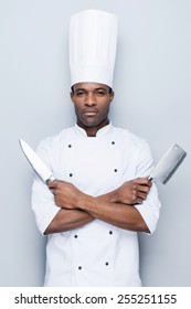 Ready to work. Confident young African chef in white uniform holding knifes in his hands and looking at camera while standing against grey background