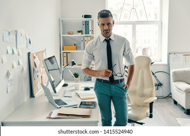 Ready to work. Good looking young man looking at camera and smiling while standing in the office